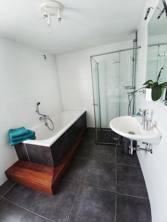 Salle de bain avec baignoire xxl, douche à l'italienne et lavabo.