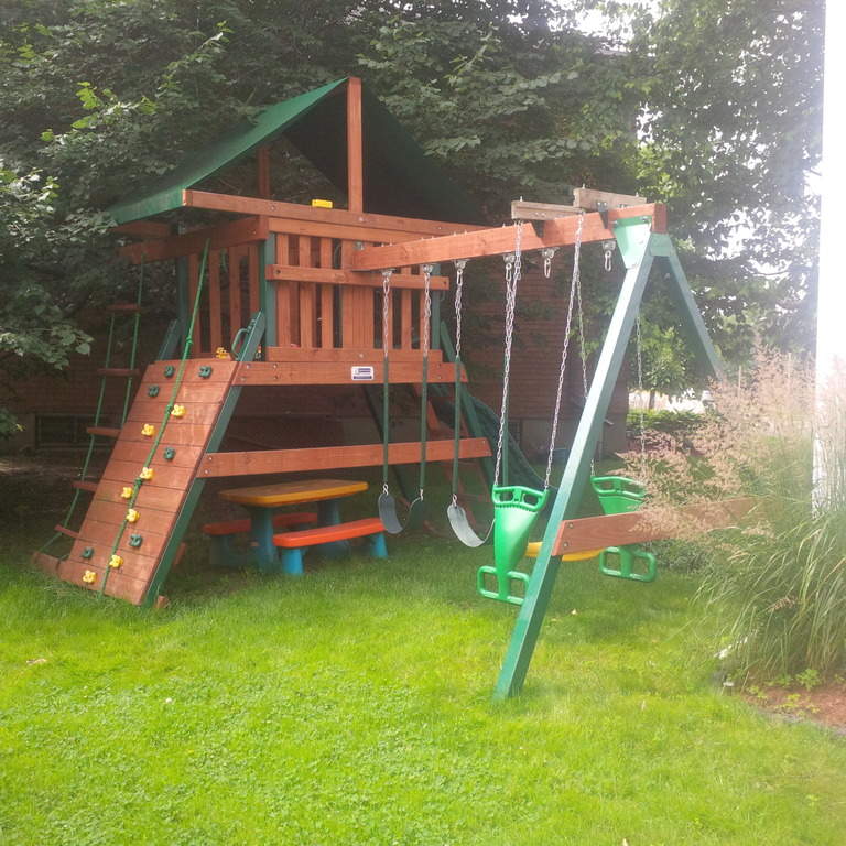 Backyard hideout, with climbing wall, slide and swings