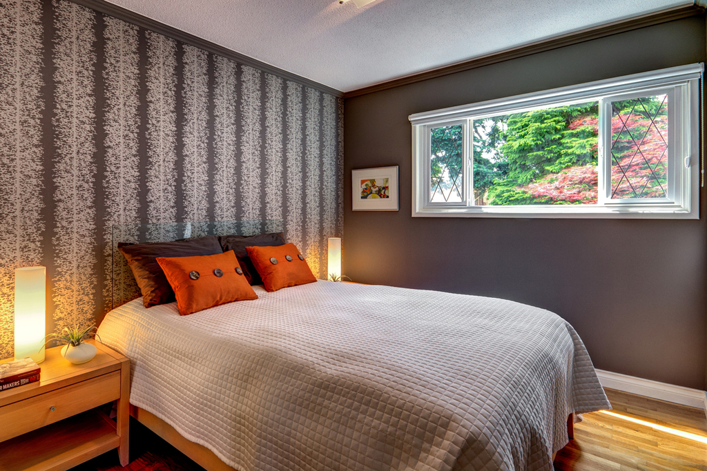 Luxurious Queen size bed with deluxe linens looks out to the treetops