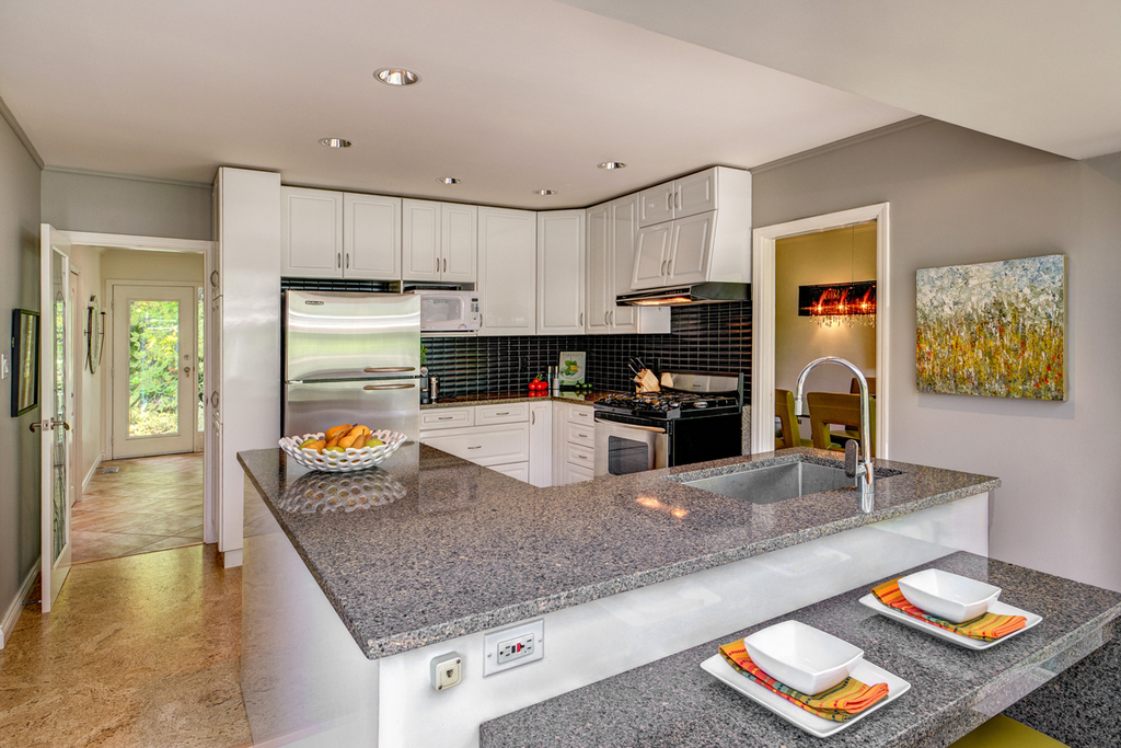 Modern well-equipped kitchen with breakfast bar, gas cookstove & leather bar stools