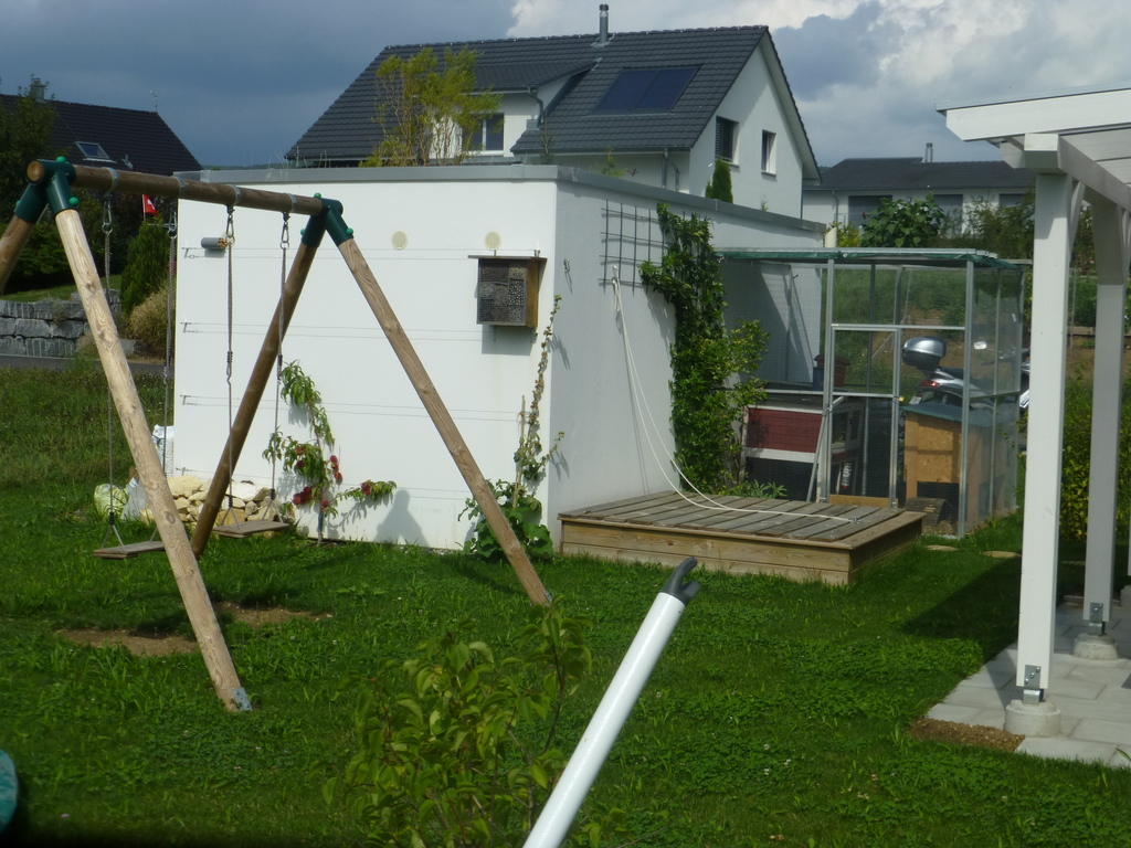 garden with sandbox, rabbit cage and swing