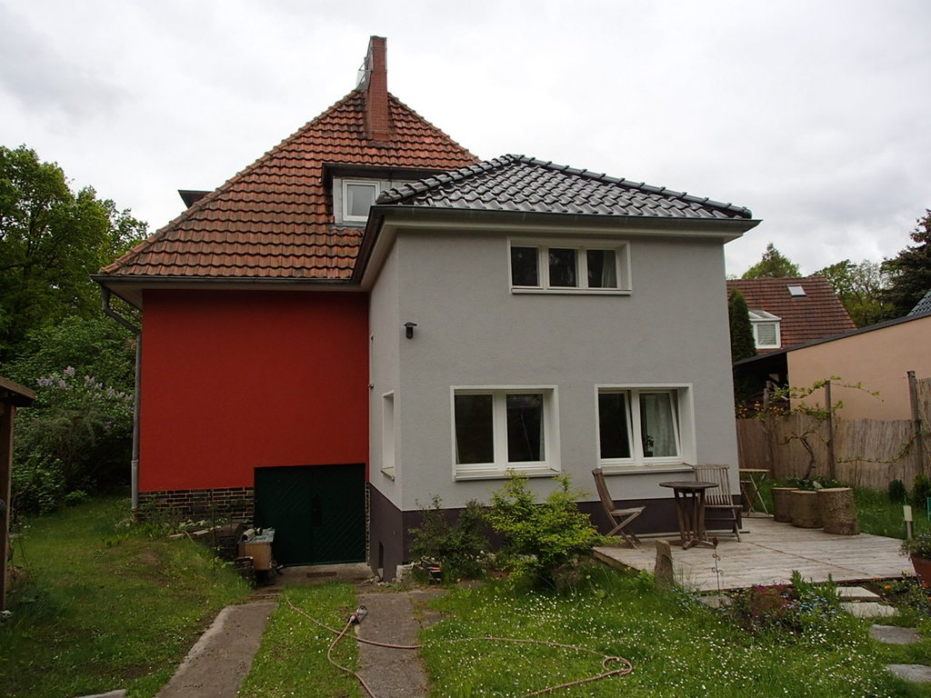 das vorderhaus in grau besteht aus 1 schlafzimmer und einem gemütlichen wintergarten