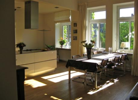 The flat is nearly 100 qm , in 3 rooms with a bath  in an old house ,here the dining table and kitchen