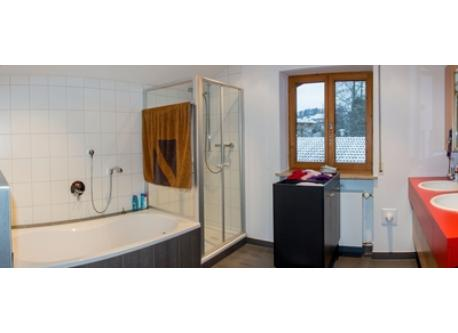 Bathroom with toilet, bath tub, shower, two washbasins and floor heating