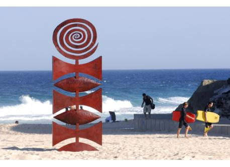 Sculpture and surfers at the beach