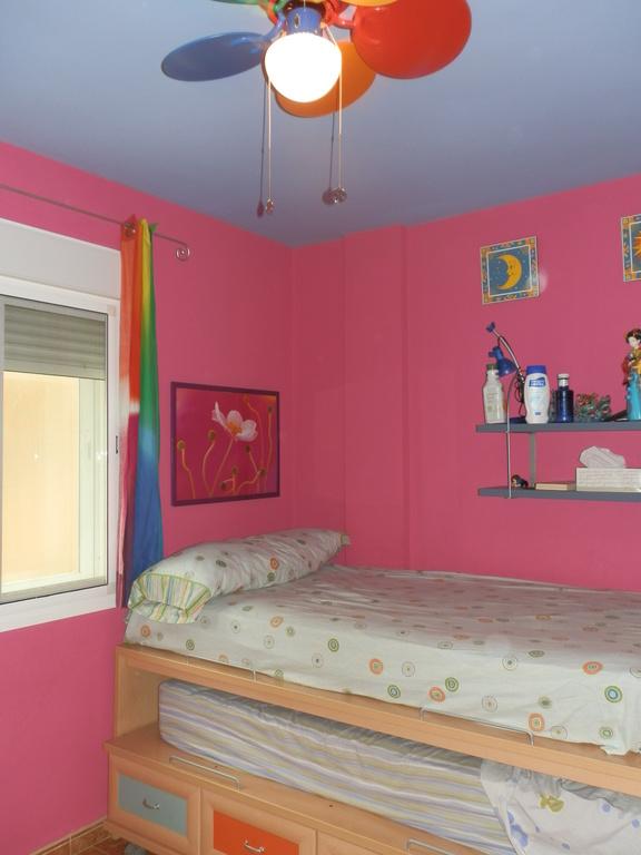Dormitorio con armario y dos camas y ventana al exterior