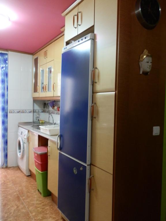 Cocina con lavadora y frigorifico.
