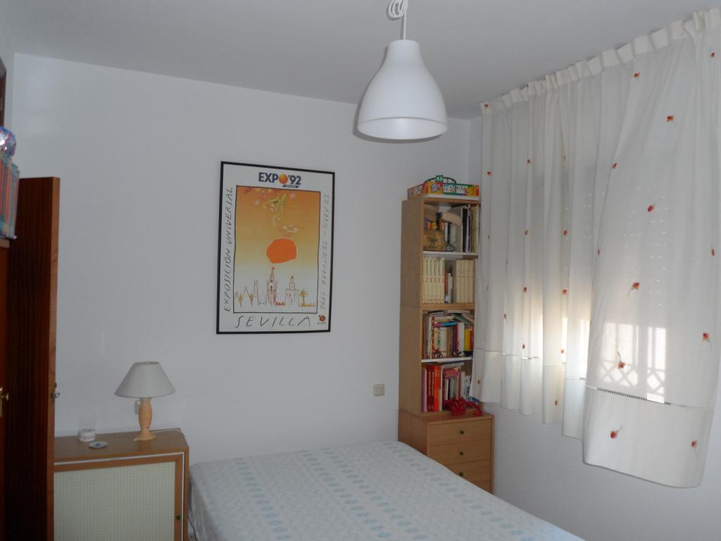 dormitorio con ventana a patio trasero y escalera a la azotea