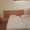 Habitación con dos camas y una amplia  cajonera