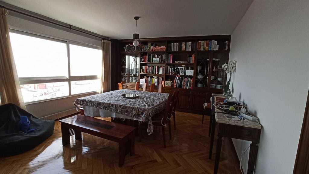 Parte derecha del salón, una mesa grande para comer viendo el mar
