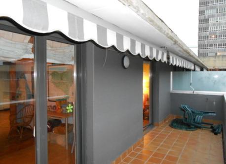 Terraza con mesa y toldo