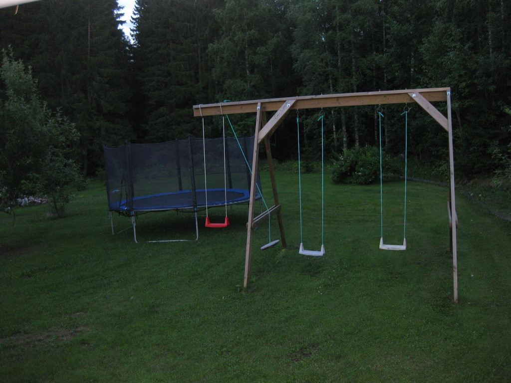 Swing and trampoline behind the house
