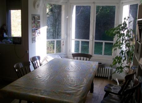 Dining room with a big table (1-12) , an old piano and a bow window