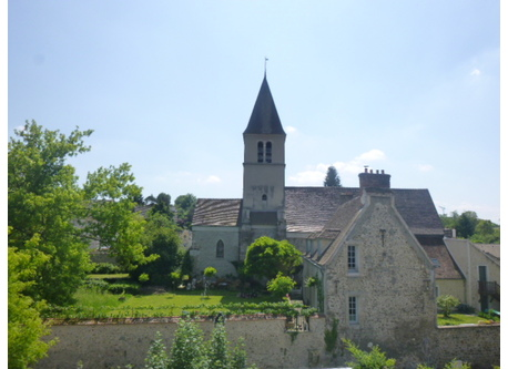 Vue de la rue sur la maison, le jardin et l'église