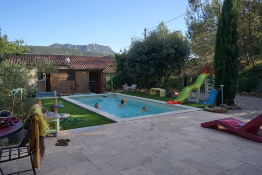 La terrasse, le jardin, la piscine et en arrière plan la montagne de la Loube