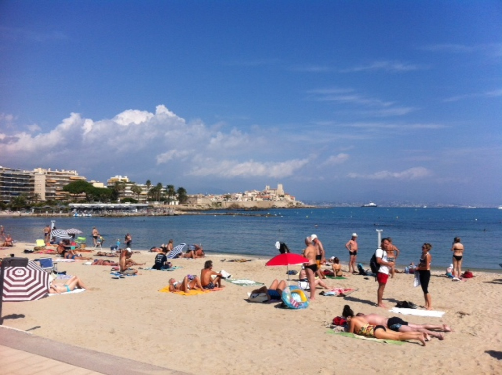 Beach in Antibes with old town in the background.