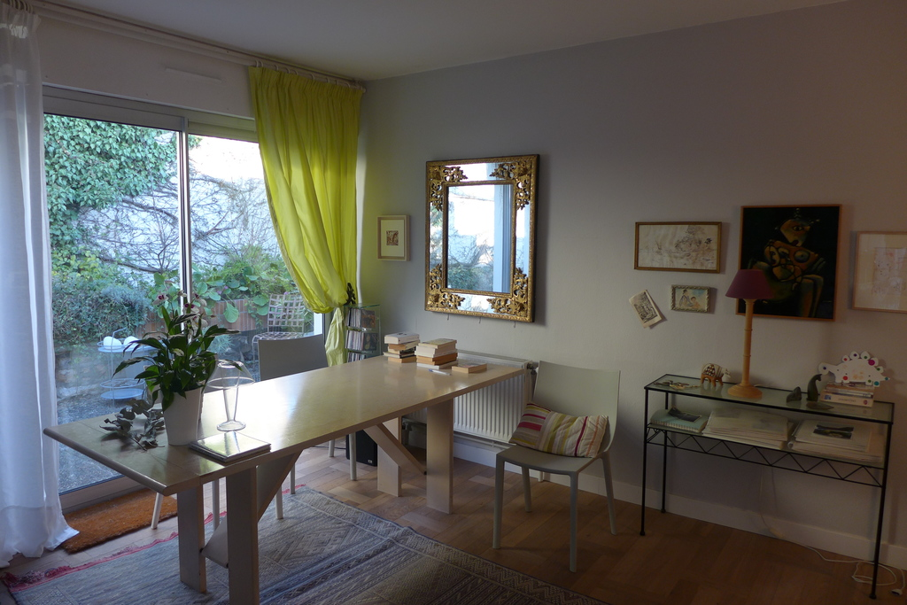 Living room with French window opening to terrace and leading to the small garden that surrounds the house