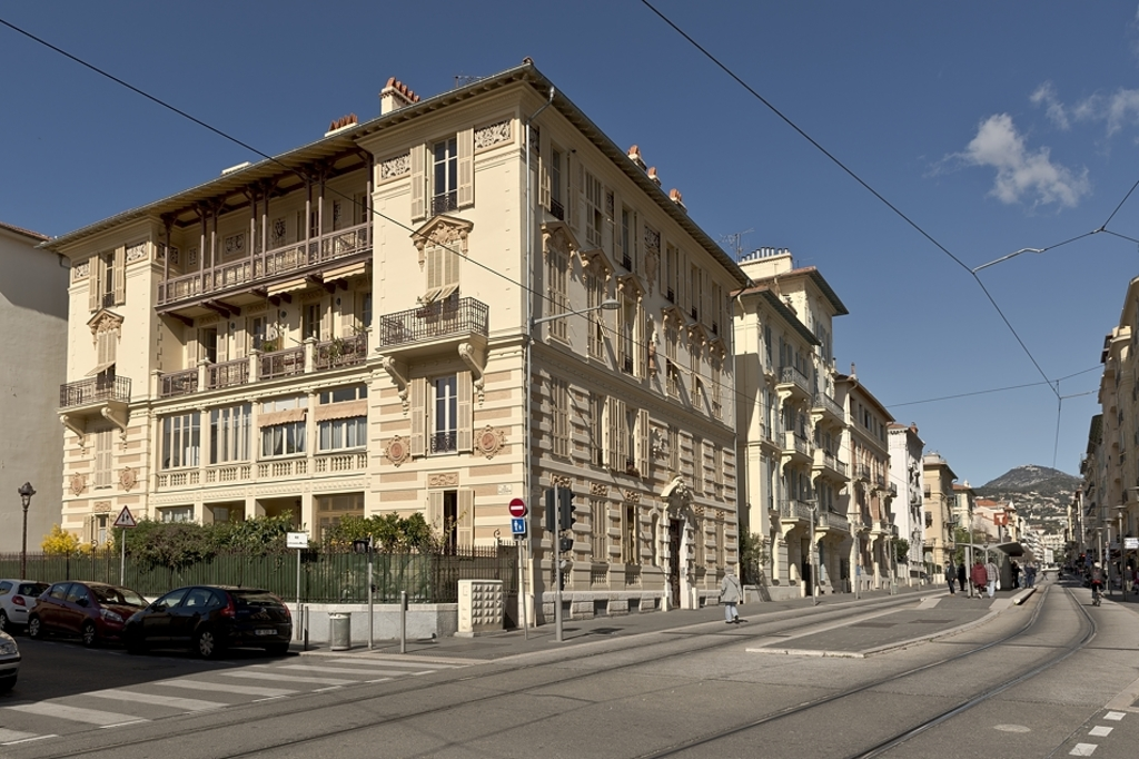 The building in Nice, with the tram stop in the middle of the street and Mont Chauve in the background.