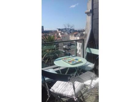 Balcon avec vue sur palmier et toits de La Rochelle