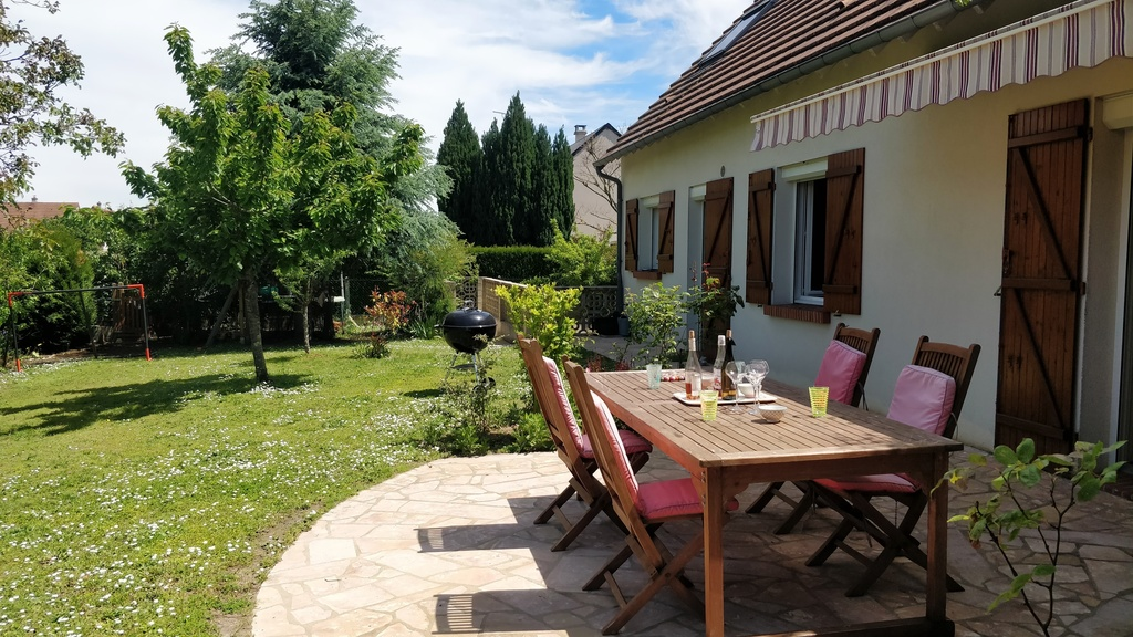 Garden back to the house with terrace, sunscreen, garden furniture and BBQ