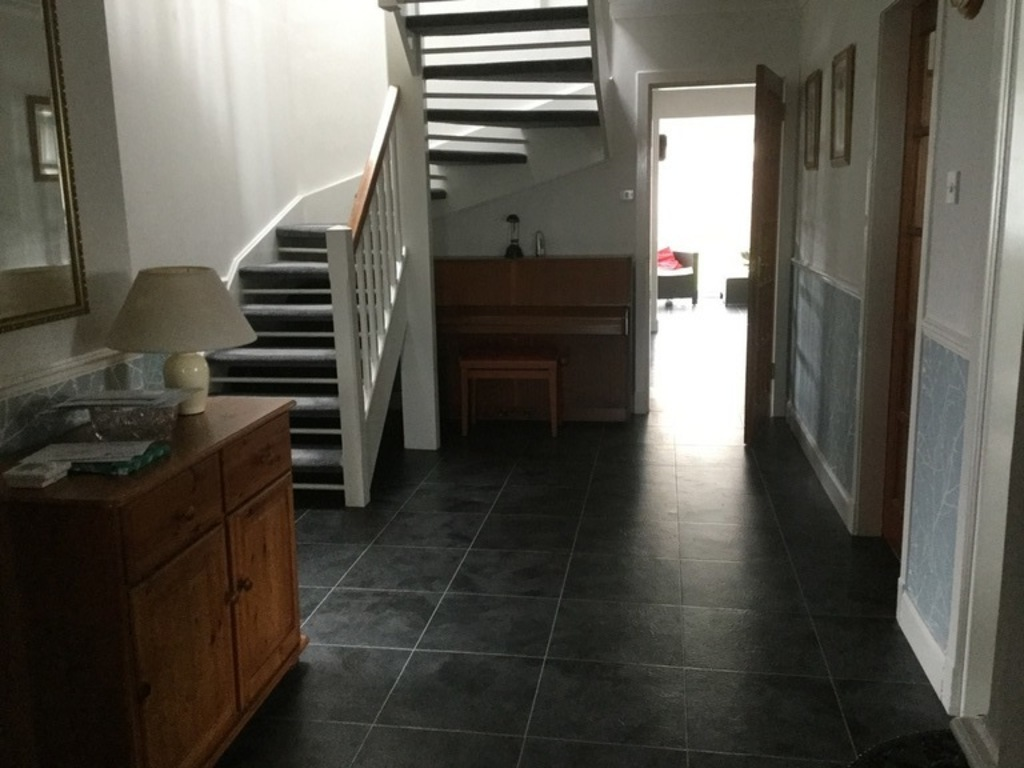 Hallway with stairs to bedrooms and door to kitchen area