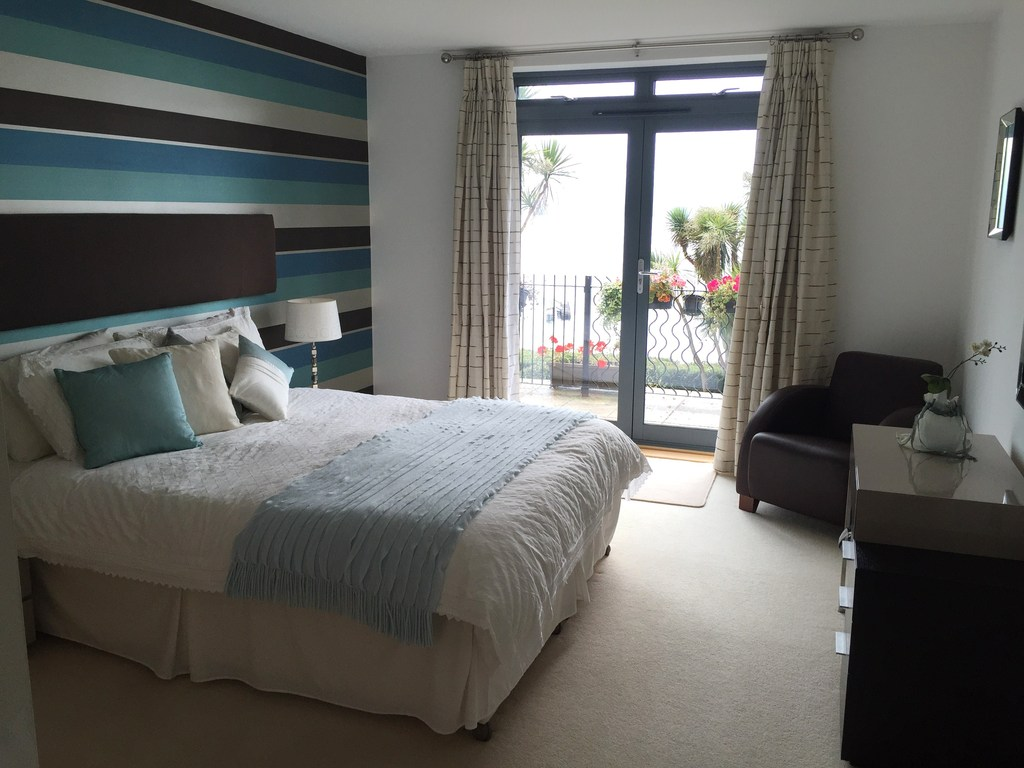 2nd bedroom overlooking the bay with access to private patio overlooking the sea. Steps through garden to the sea front.