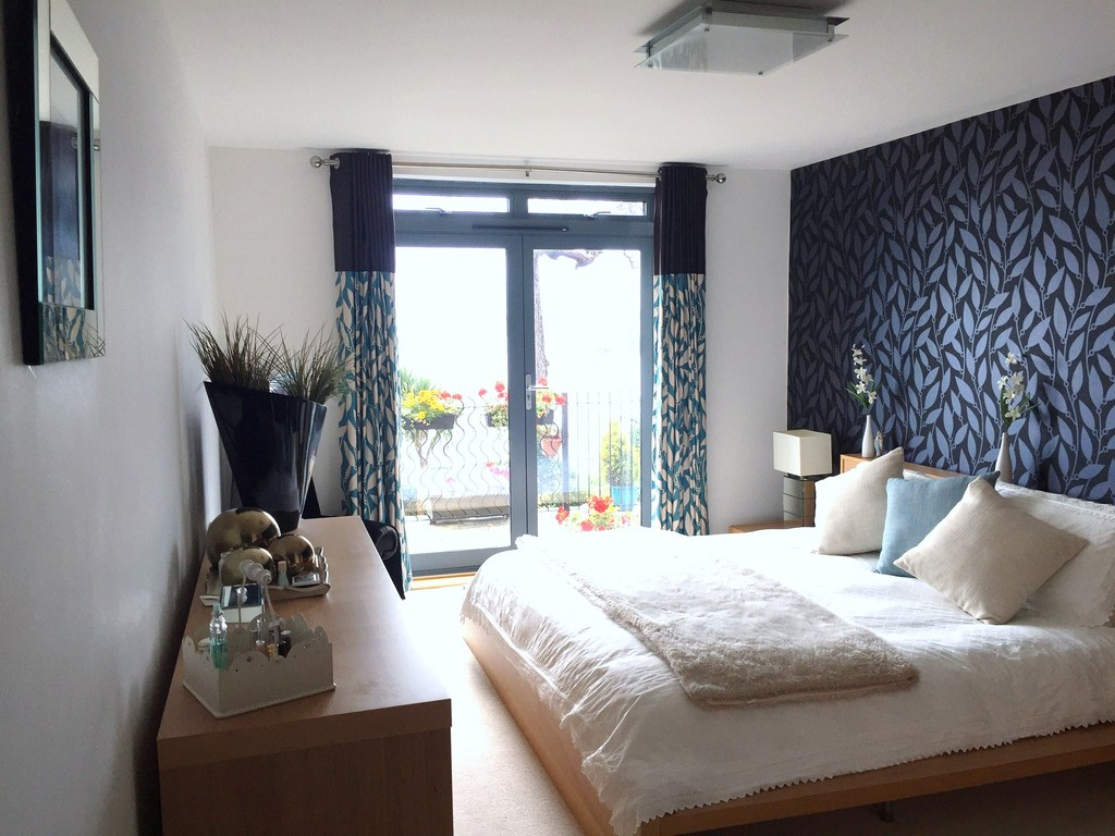 Main en-suite bedroom overlooking the bay with access to private patio, on garden level. Steps to sea front through the garden