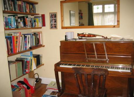 Front room with piano and wood burning stove for winter