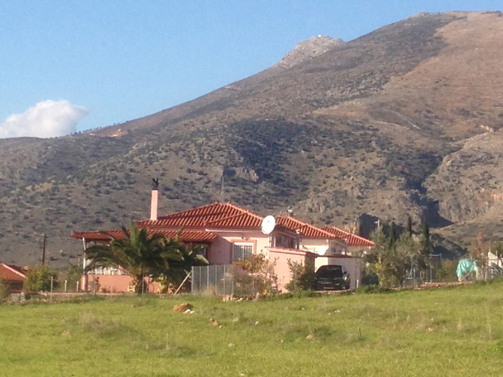 The house is surrounded by mountains, olive-and orange trees.