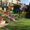 kids slide into garden, playhouse, bbq and trampoline