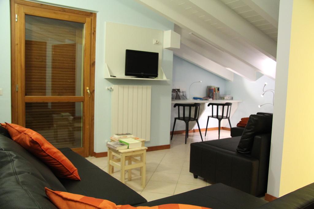 Zithoek boven met TV, 2 dubbele zetels, kolomkast, bureau en deur naar balkon.