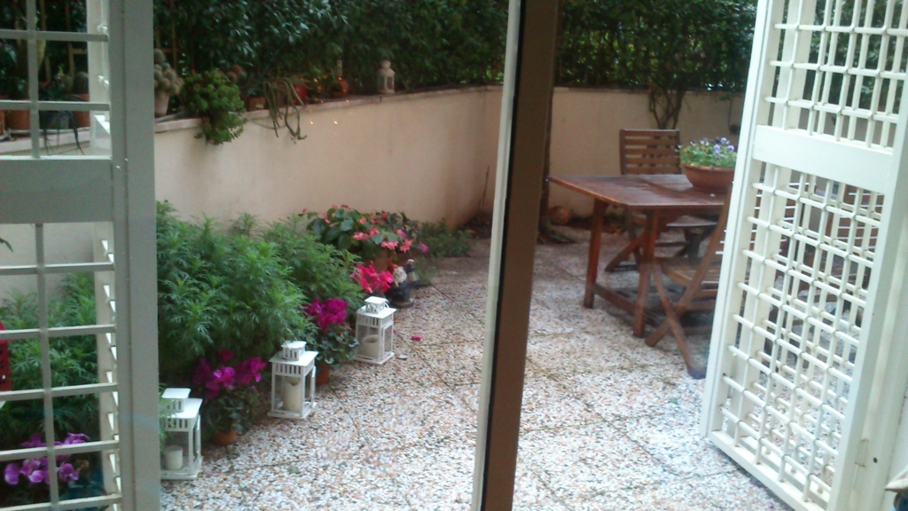small terrace in front living room and kitchen with a table to eat during the summer