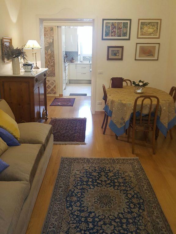 Soggiorno dell'appartamento con cucina in fondo separata da parete scorrevole finemente decorata