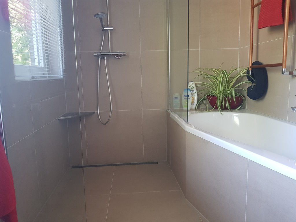 bathroom with walk in shower and bath on the first floor