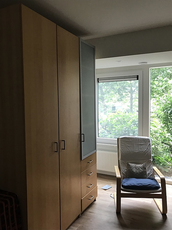 Single bedroom window view and cupboards
