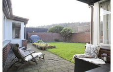 Small secluded garden with strawberry cultivation and bbq in the background
