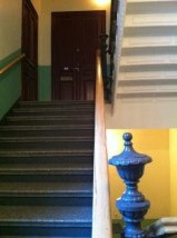 Stairs leading to our door on 2nd floor, with original 1890-railing and knob