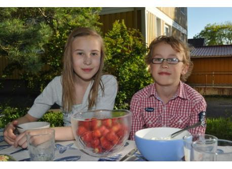Edith and Alve in the garden eating a typical swedish desert, strawberries with cream.