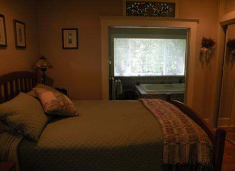 "Master bedroom in ""old house"" with private bath and jacuzzi;  in the background is a large window overlooking the back yard"