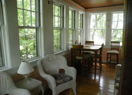 All-season porch with dining table overlooking Chester Brook - most beautiful eating spot in town