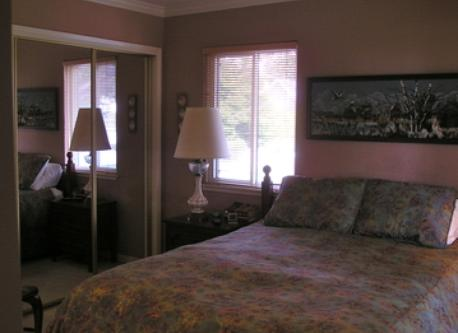 Large bedroom opens to sunroom and has double closet and wall unit for clothes storage