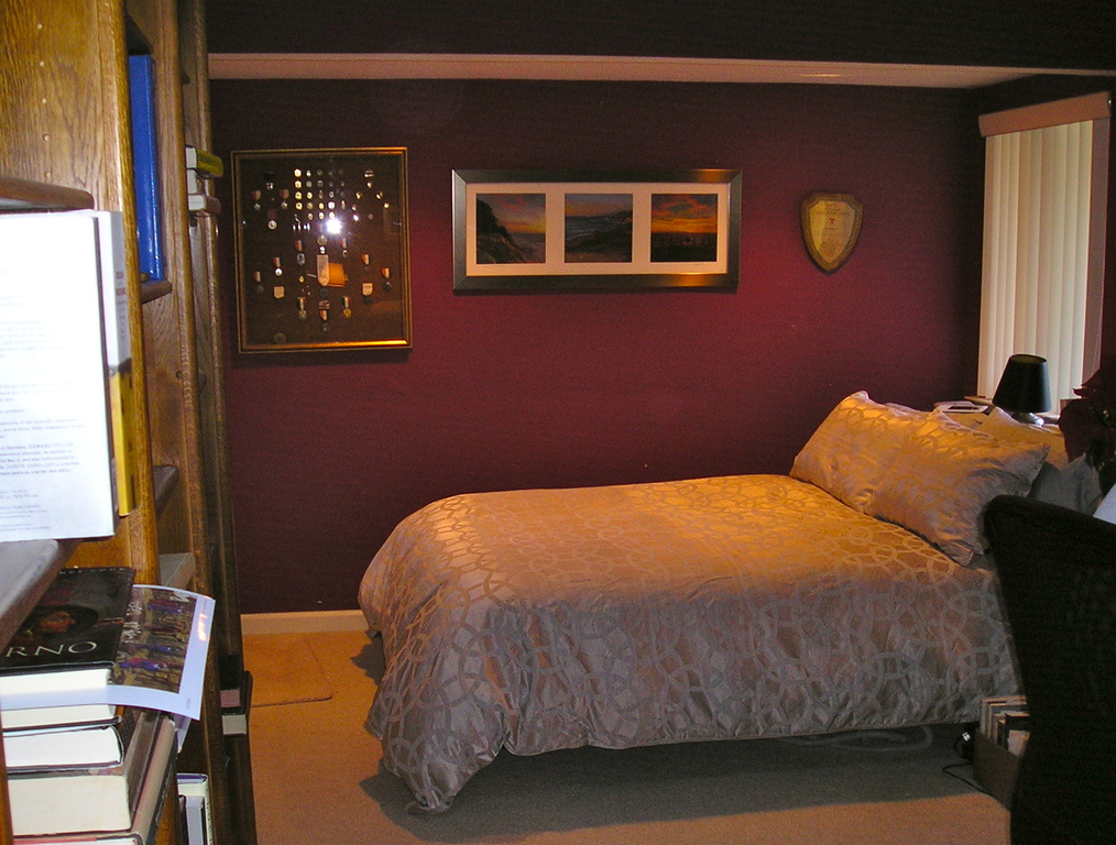 Large bedroom with office, wall of bookshelves, and private bath.