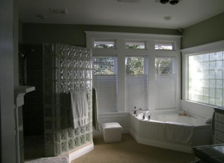 Master bath with walk in shower with two shower heads and large oval tub and two sinks