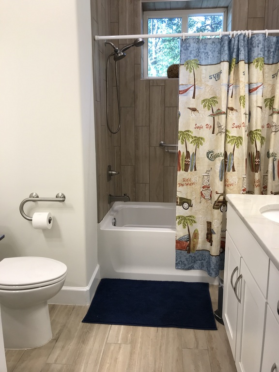 Bathroom downstairs with bathtub and two sinks