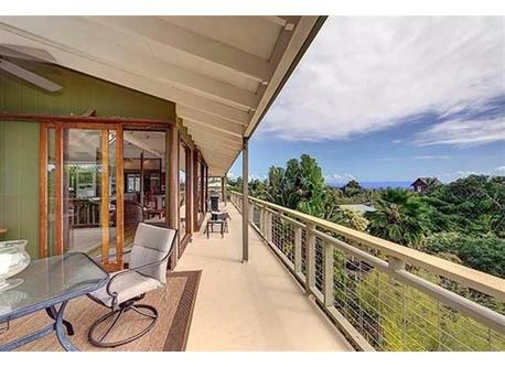 This unique second-floor one-bedroom house is surrounded by a large lanai (porch).