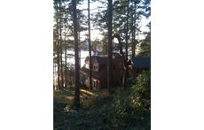 Our cabin nestled among the trees, near the water's edge.