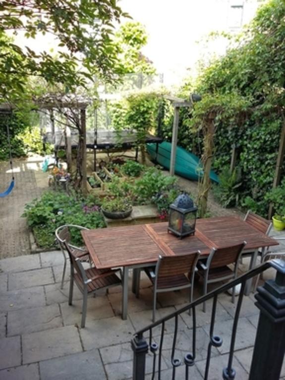 onze tuin, met kleine groentetuin, trampoline en de kano