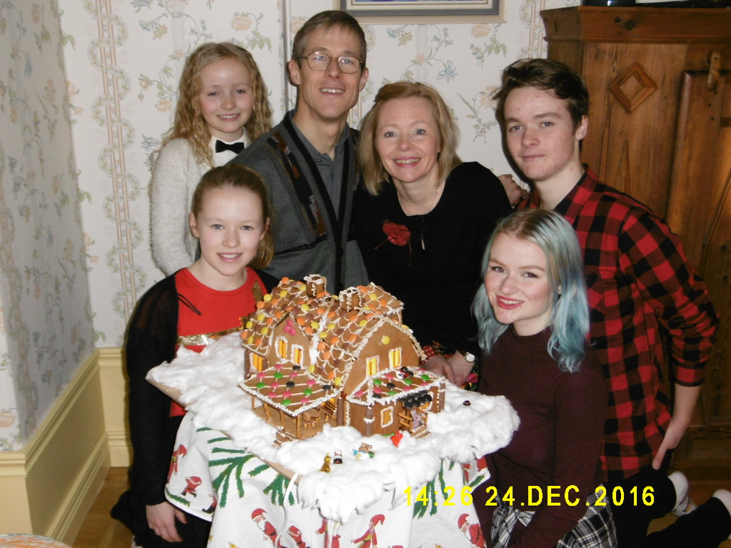 Our family at Christmas, with a gingerbread house model of our house.